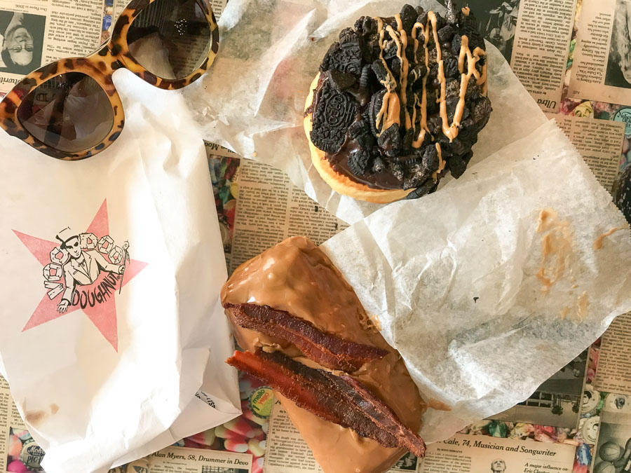 old dirty ba***rd - raised yeast doughnut with chocolate frosting, Oreo cookies, and peanut butter (right). Bacon maple bar - raised yeast doughnut with maple frosting and bacon on top (left) at Voodoo Doughnut, Austin