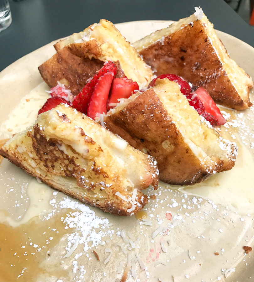 the OMG french toast at Snooze, Austin. Fresh brioche stuffed with mascarpone and topped with vanilla crème, salted caramel, fresh strawberries and toasted coconut.